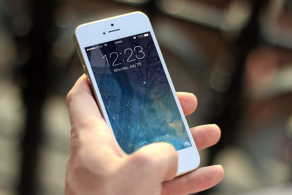 O mână în care se află un telefon mobil.