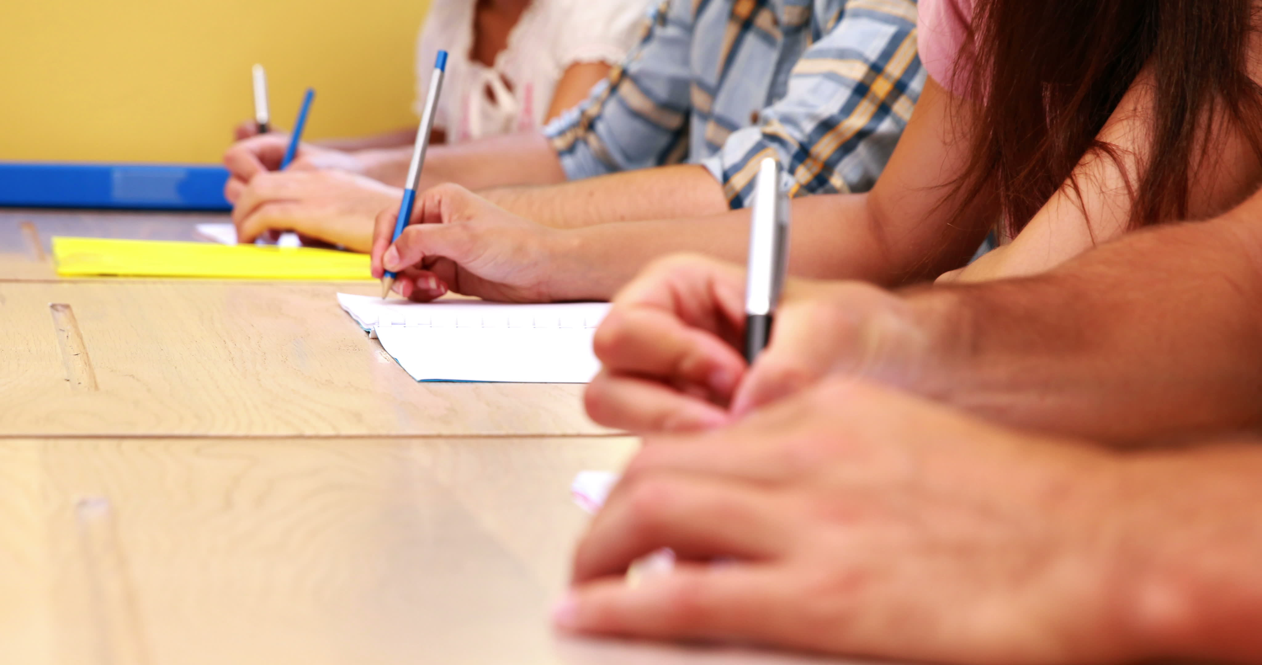 Elevi care scriu în clasă, așezați în bănci.