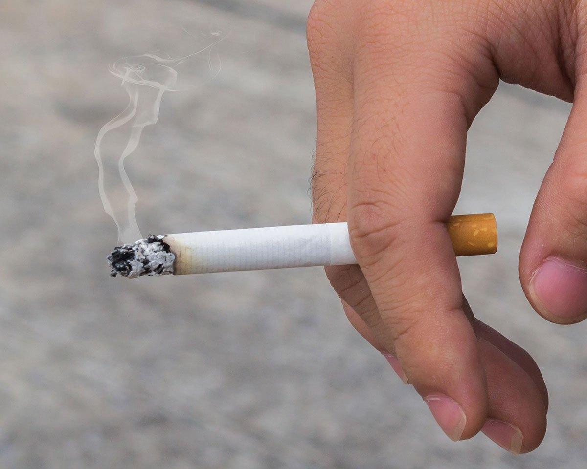Mână în care se află o țigară aprinsă.