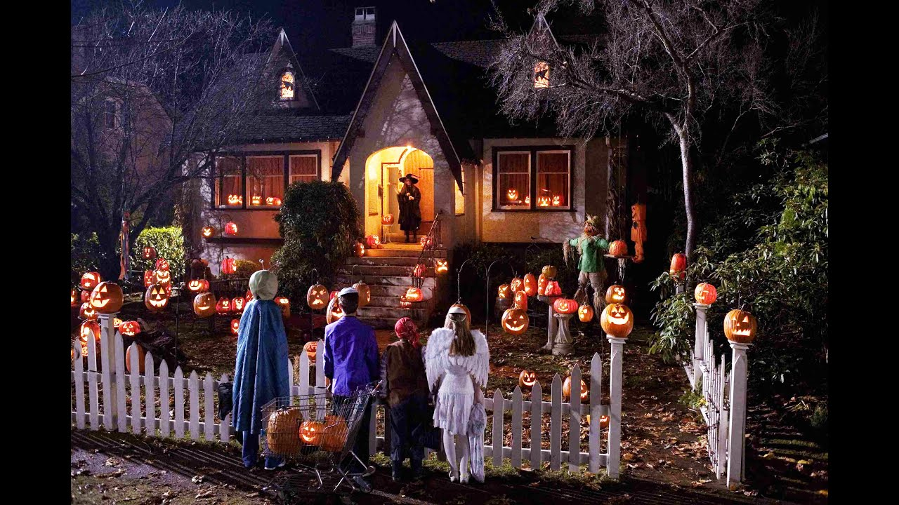Casă decorată pentru sărbătoare de Halloween, la poarta careia sunt copii mascați care așteaptă dulciuri.