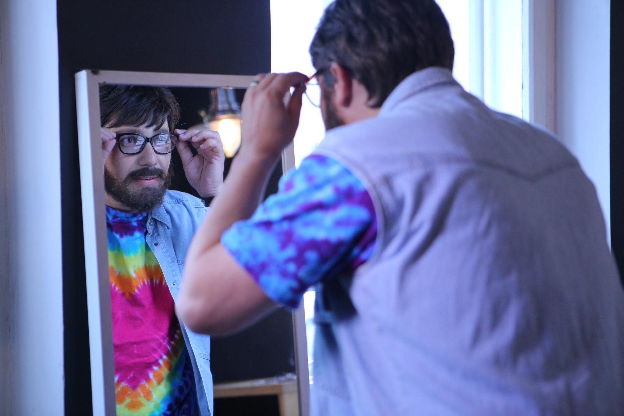 Bărbat cu ochelari care se uită în oglindă.