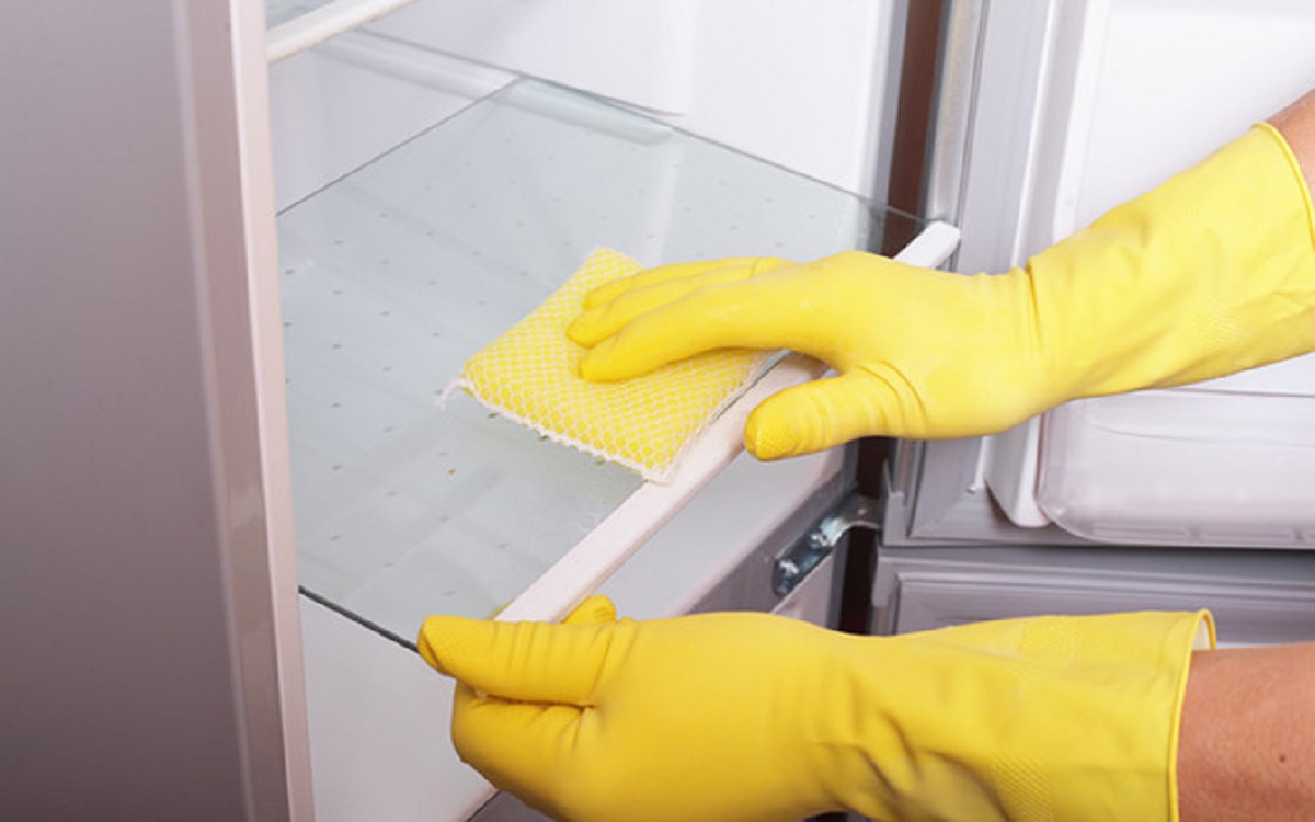 Două mâini cu mănuși care curăță un frigider.