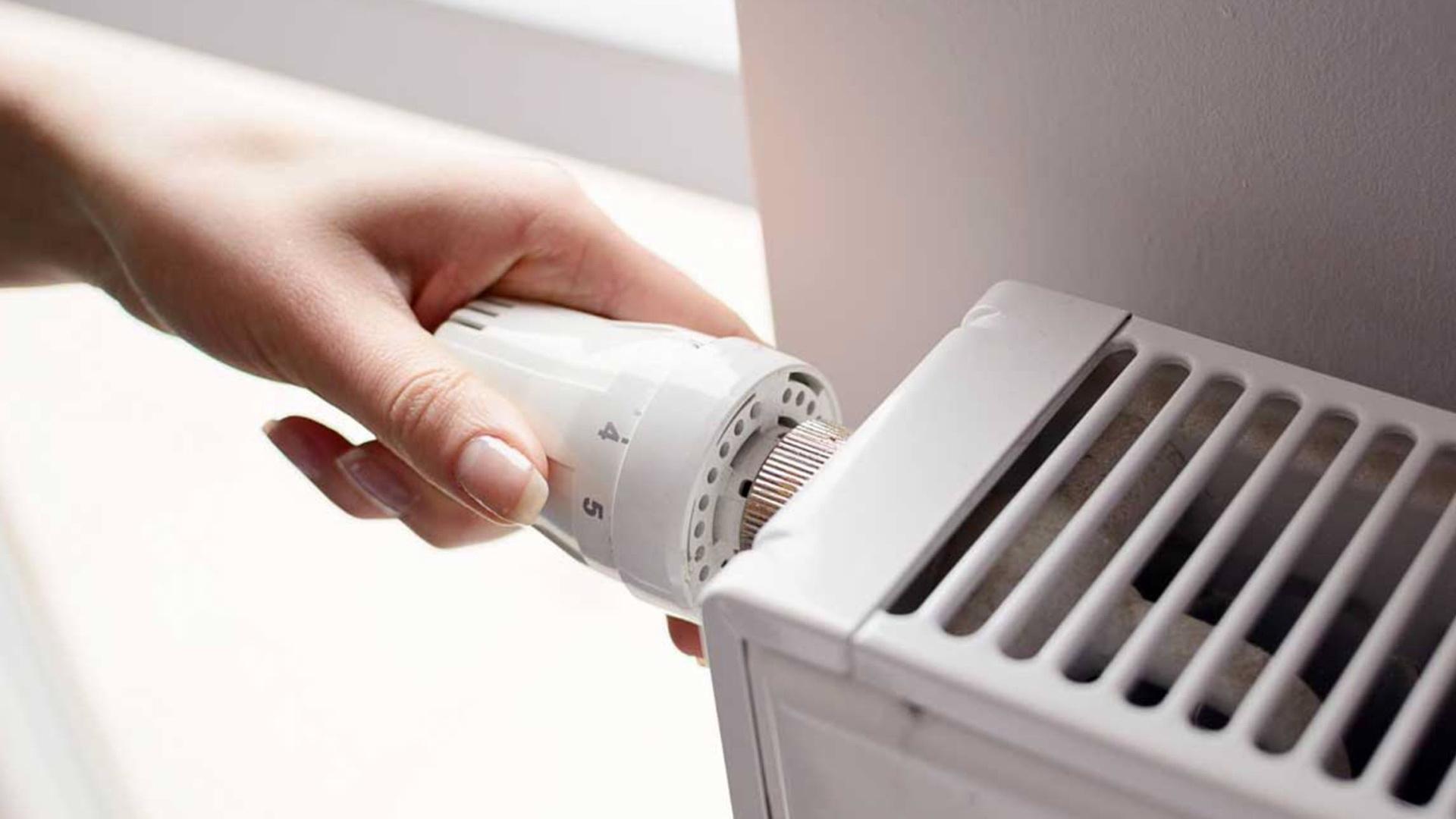O mână care reglează un calorifer.