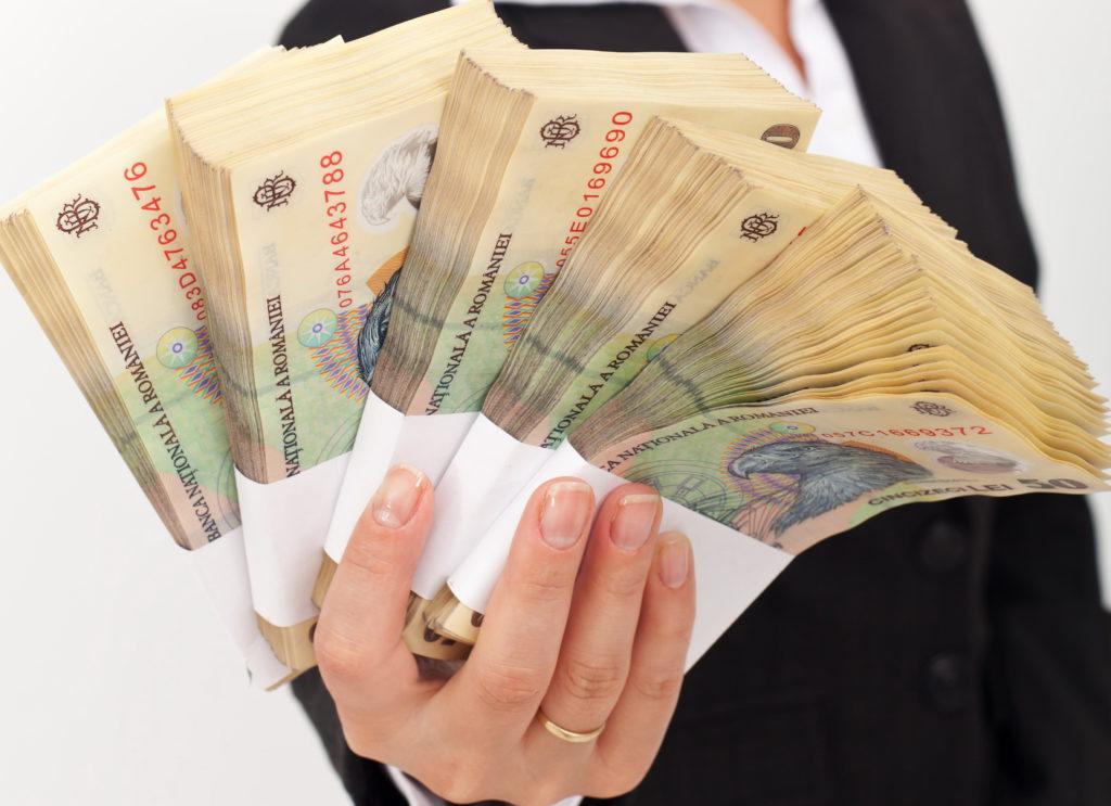 O mână în care se află teancuri cu bani.