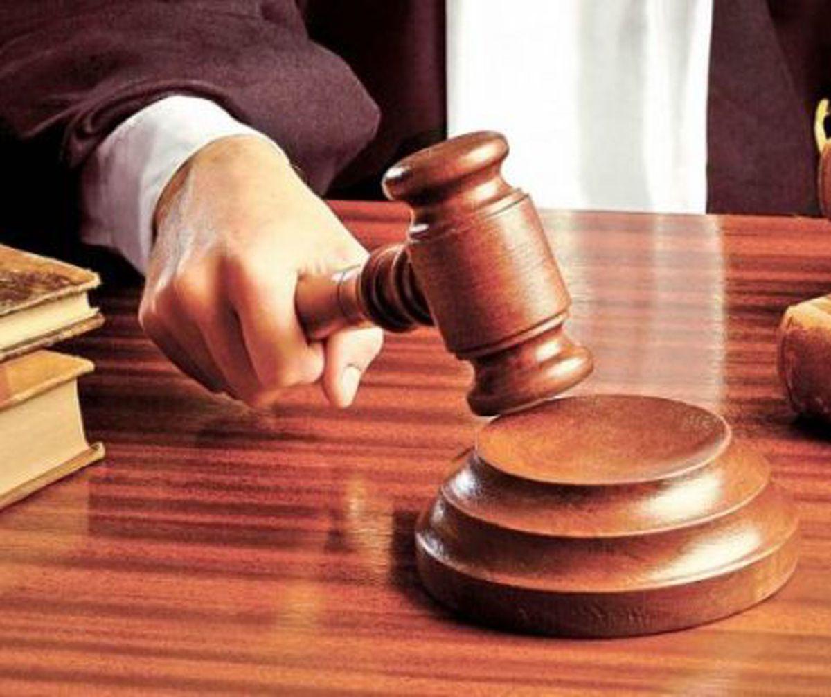 Judecător cu ciocan din lemn în mână, pronunțând sentința.