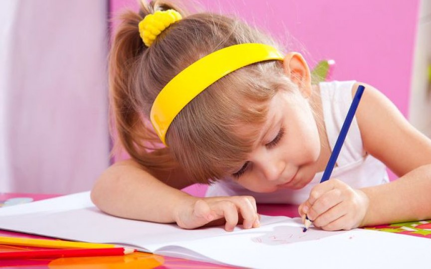 Copil cu creion în mâna stângă
