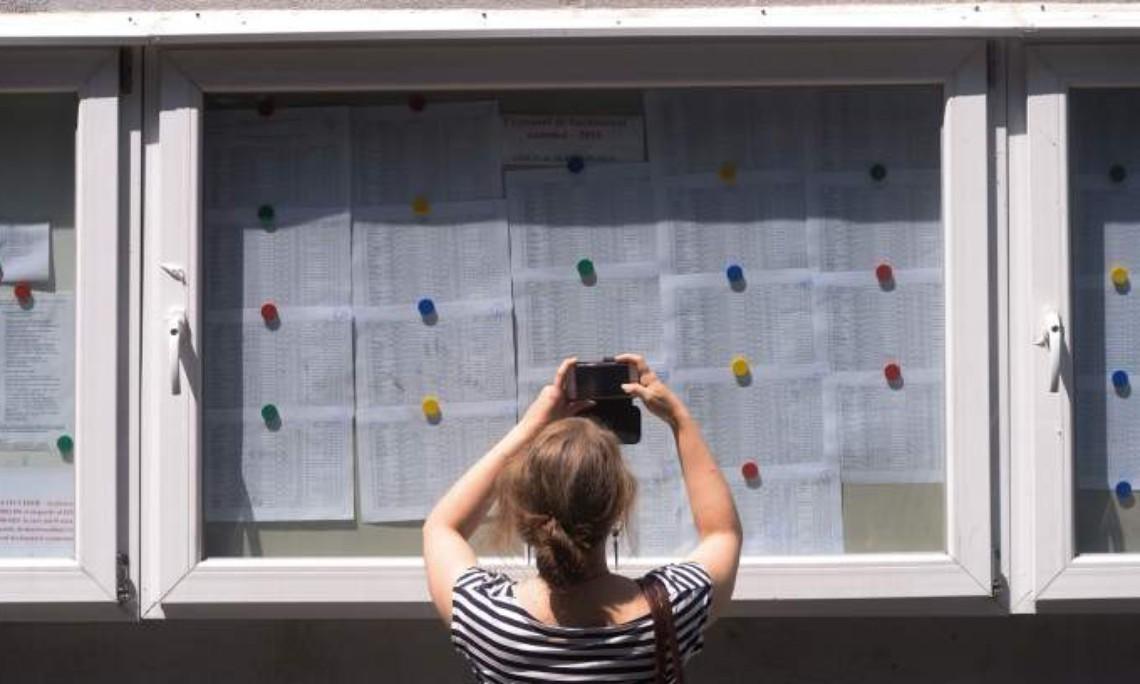 Elevă care verifică notele de la Bacalaureat la avizier.