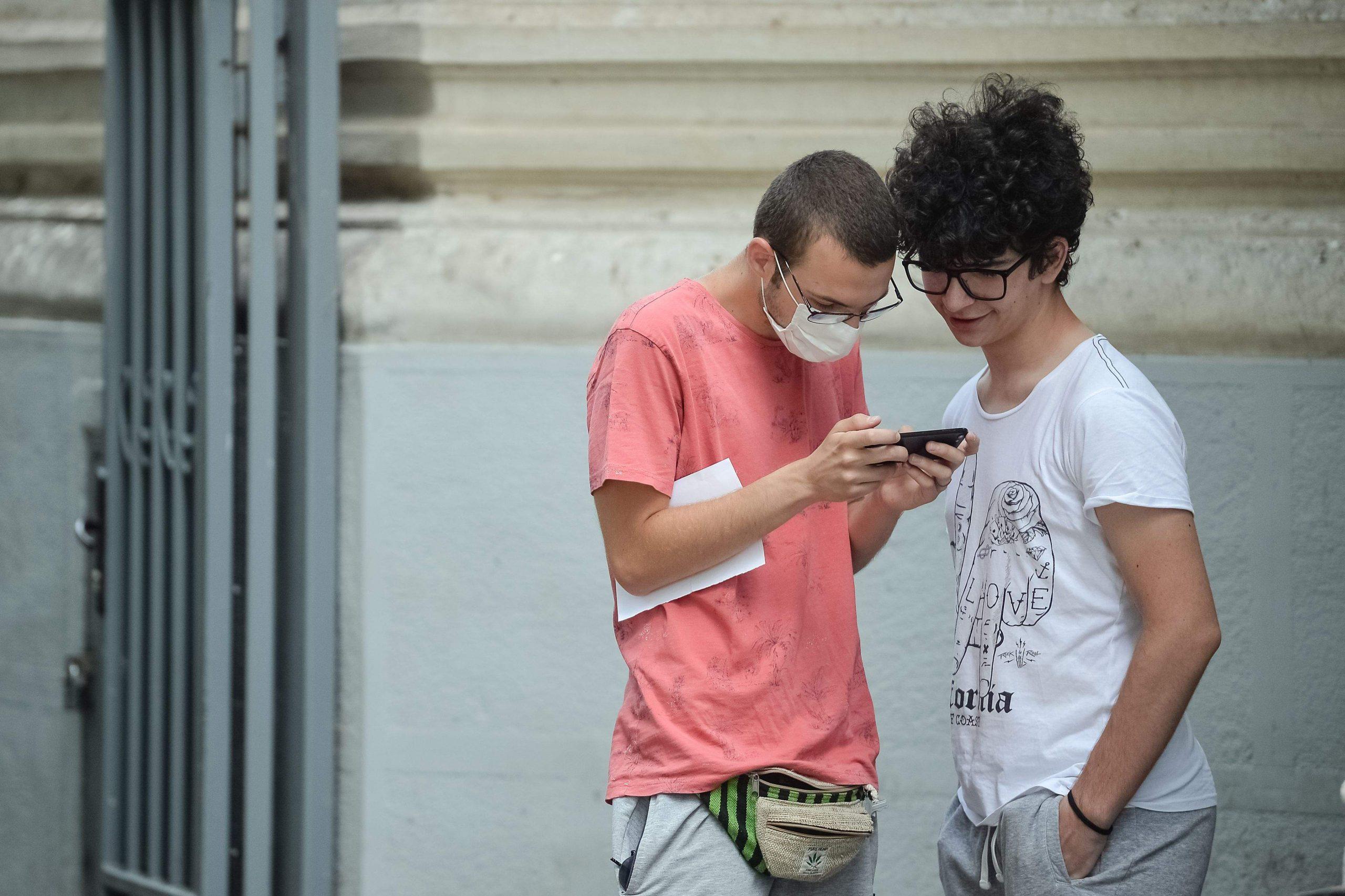 Doi elevi care verifică rezultatele de la examen pe telefonul mobil.