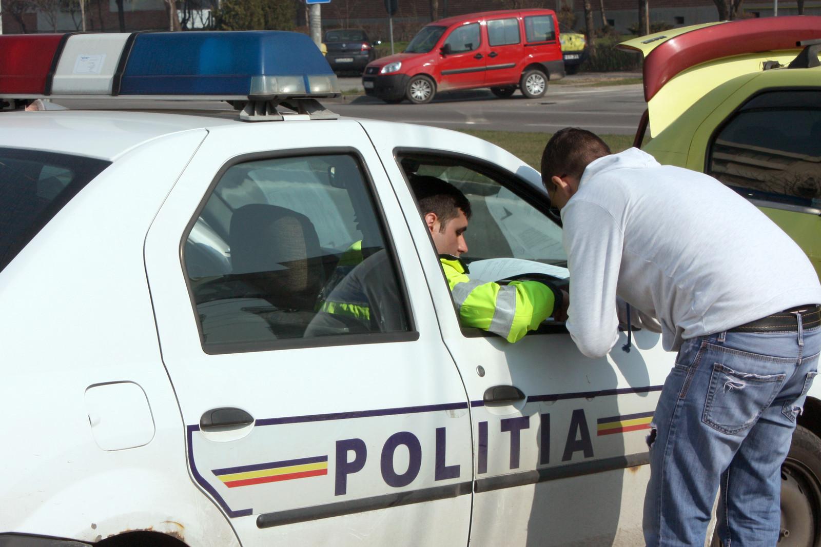 Bărbat aplecat la geamul unei mașini de poliție