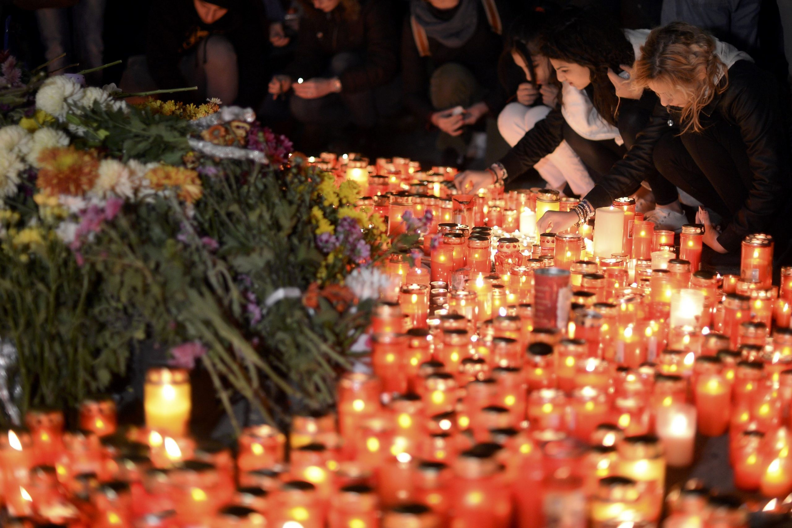 Lumânări aprinse și oameni care plâng