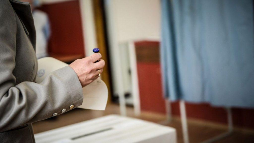 O persoană aflată lângă urnă cu buletin de vot și ștampilă în mână.