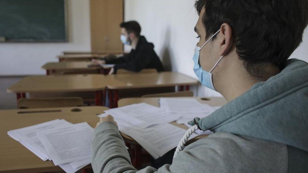 Elevi cu masca de protecție în bănci
