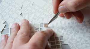 Omul care construiește orașe din hârtie tăiată milimetric