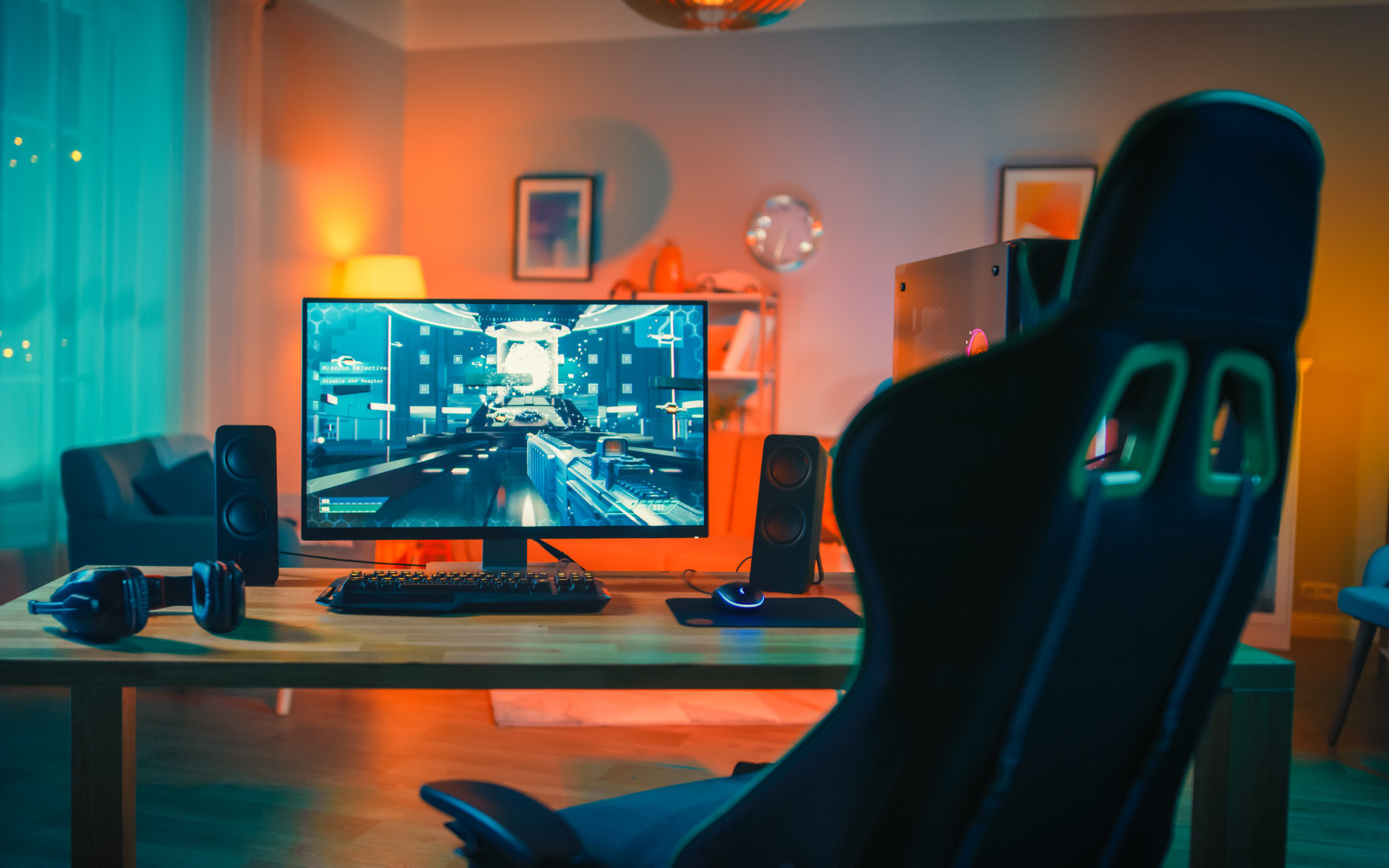 Powerful Personal Computer Gamer Rig with First-Person Shooter Game on Screen. Monitor Stands on the Table at Home. Cozy Room with Modern Design is Lit with Warm and Neon Light.